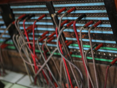 A photograph of an old telephonic relay with qires inserted into a board connecting up phone lines in a seeminlgy random pattern
